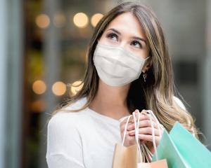 Portrait of a thoughtful Latin American woman shopping at the mall during the pandemic and wearing a facemask while holding bags